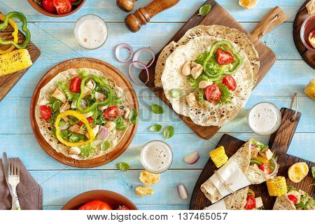 Tortilla wraps with grilled chicken fillet lager and grilled vegetables on blue wooden table. Top view. Outdoors Food Concept