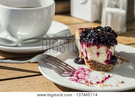 Bite of yummy blackcurrant cheesecake with fork and tea
