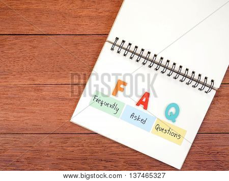 Word spell FAQ and handwriting frequently asked questions on notebook with dark wood background on top view