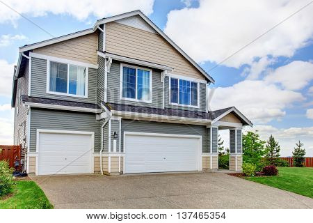 Large two story house with siding two garage spaces and concrete driveway. House exterior.