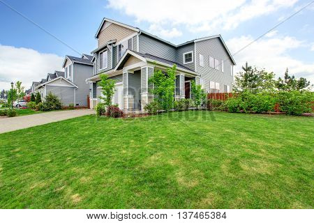 Beautiful Curb Appeal Of Large Blue House And Green Front Yard.
