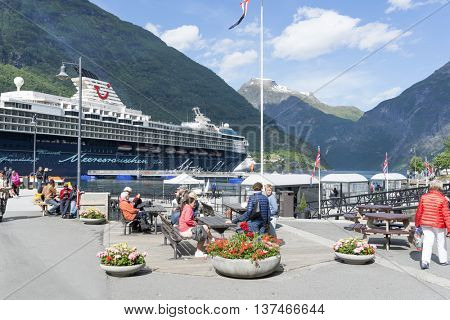 GERANGER, NORWAY - JUNE 29: Cruise liner in Geirangerfjord sea port with tourists on June 29, 2016 in Geiranger, Norway. Geirangerfjord is famous place and UNESCO heritage site.
