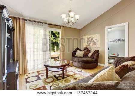 American family room with brown sofa set rug glass top coffee table and vaulted ceiling.