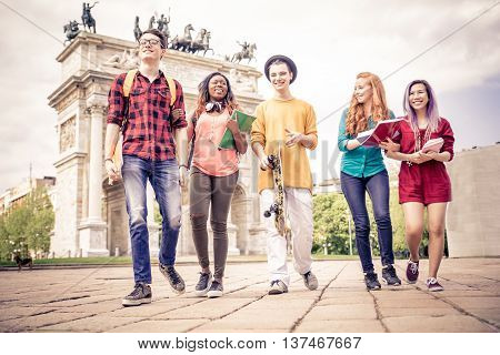 Multi-ethnic group of teenagers walking outdoors and having fun - Group of friends meeting while going to school