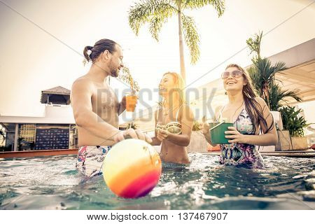 Group of friends having party in a swimming pool - Happy people enjoying summer vacation