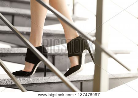 Woman walking up some stairs.