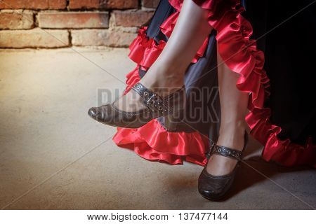 Close up view of legs of woman sitting on a chair and dressed in costume of Flamenco dancer. The photo has deliberately darkened edges. Horizontally.