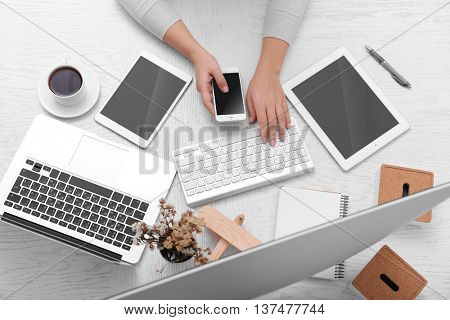 Concept of using electronics. Businesswoman works at office, close up. Computer, laptop, tablet, cup of coffee and other things on the table. Top view