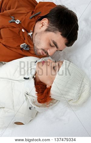 Young couple lying and kissing on the snow outdoors in winter, close up