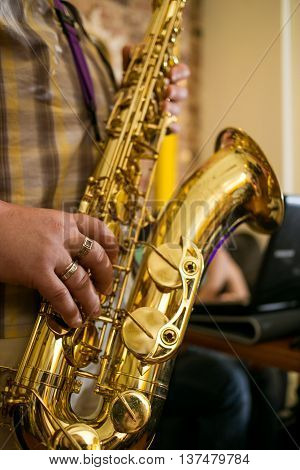 Saxophone jazz music instrument Tenor sax saxophonist hands Closeup saxophone player.