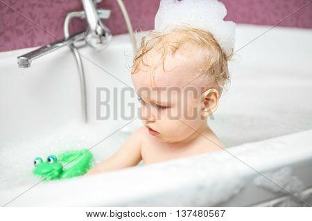 Cute baby boy with foam in bath