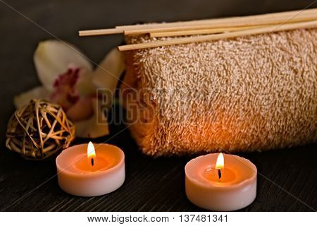 Beautiful spa composition with towel and lighted candle on dark table