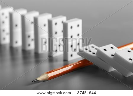Dominoes and pencil on grey background