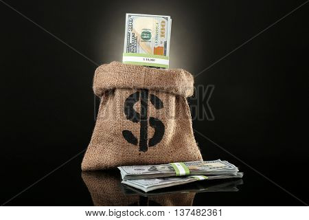 Money bag with dollars on black background