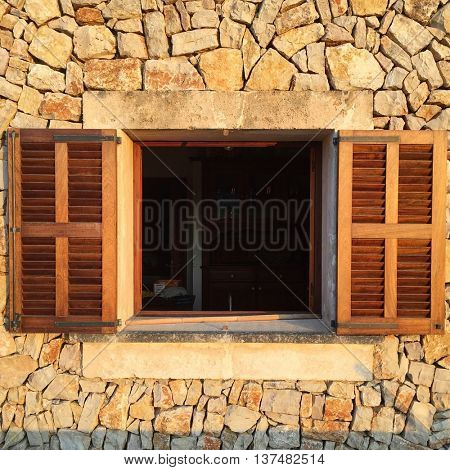 Stone wall and window with open wooden shutters