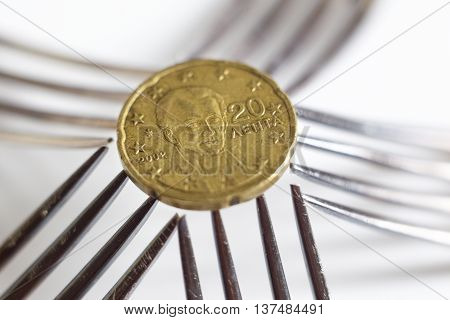 20 euro cents seen over five silver forks.