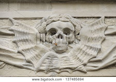 stone relief skull with cigarette. smoking kills concept.