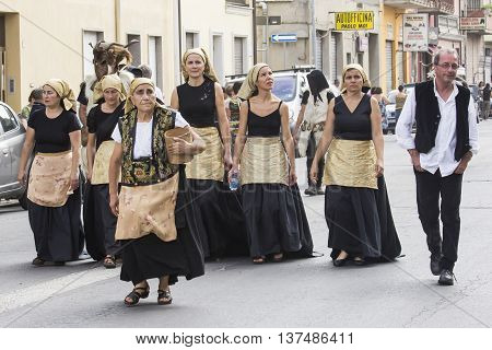 QUARTU S.E., ITALY - September 21, 2014: Parade of Sardinian costumes and floats for the grape festival in honor of the celebration of St. Helena. - Group of people in traditional Sardinian costume