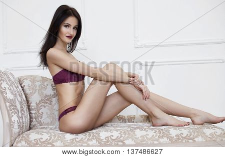 Slim beautiful brunette woman laying on sofa. Lady with long leg.