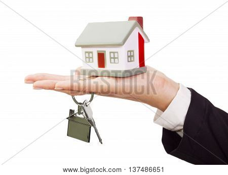 Miniature model house and keys resting on a female hand