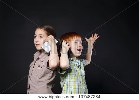 Portrait of happy, smiling girl and boy speak on mobile phones at black background. Positive and emotional children talking to somebody, calling with cell phones. New generation devices, communication