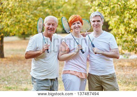 Happy seniors as a badminton team in the park