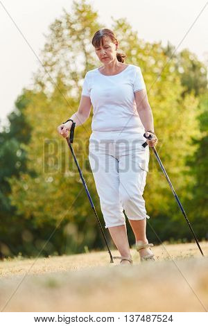Senior woman during nordic walk with walking sticks in the nature