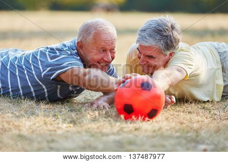 Two seniors reaching ball during soccer match in the park in summer