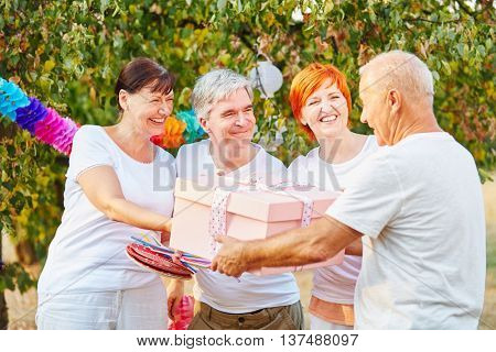 Group of happy seniors with birthday present in a garden in summer