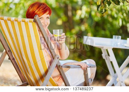 Senior woman dinking a glass of water in summer at her garden