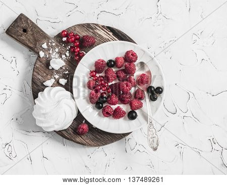 Raspberries red and blackcurrants a meringue on a rustic cutting board on bright background