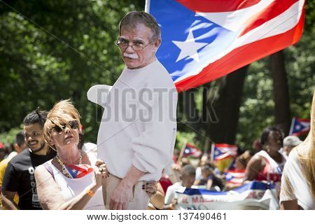 NEW YORK - JUNE 12 2016: A woman supporting imprisoned nationalist Oscar Lopez Rivera holds a lifesize cardboard cutout of him in the 59th National Puerto Rican Day Parade on 5th Ave in NYC.