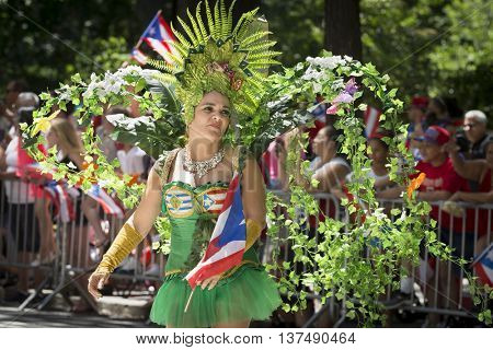NEW YORK - JUNE 12 2016: A woman wearing a traditional carnival costume marches in the 59th annual National Puerto Rican Day Parade on 5th Avenue in New York City on June 12 2016.