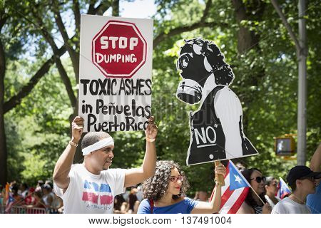 NEW YORK - JUNE 12 2016: Political message signs displayed during the 59th annual National Puerto Rican Day Parade that say Stop Dumping Toxic Ashes in Penuelas and a woman wearing a gas mask.