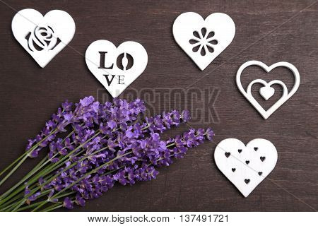A bouquet of lavender and wooden heart on a dark background.