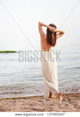 Young slim woman dressed in long white dress with open back, relaxed standing back with hands behind head
