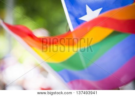 A bright photo illustration of the rainbow pattern Pride flag waving in front of a Puerto Rican flag, rippled filter effect.