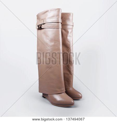 Ladies beige boots in a grey background