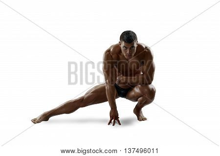 Muscular man squatted down his leg to the side. Isolated