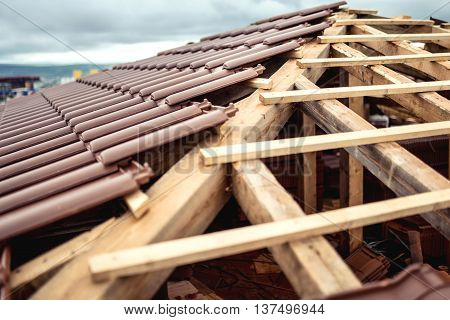 Roof Under Construction With Stacks Of Brown, Modern Tiles Covering House