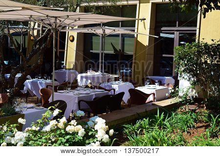 Outdoor café seating with umbrellas surrounded by plants and flowers