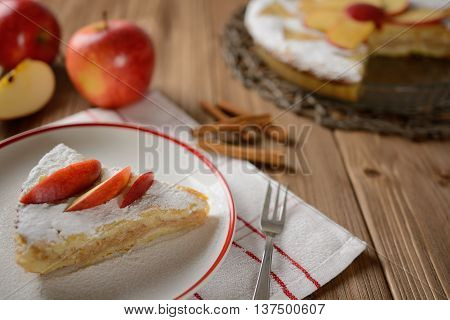 Apple pie sprinkled with sugar on a wooden background