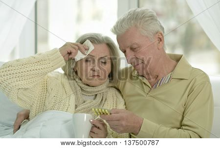 Portrait of sick  senior woman with her husband in bed