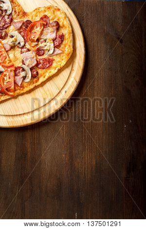 Pizza heart shape on dark wooden background top view. Thin pastry crust on wooden desk