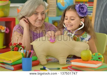 Cute little girl making art with granny