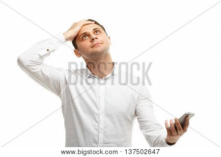 Handsome satisfied businessman using phone holding on to the head isolated on white