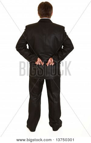 Businessman holding crossed fingers behind back isolated on white