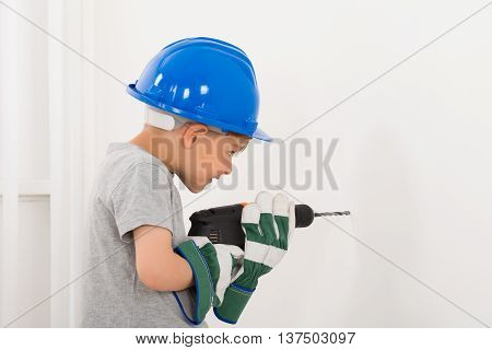 Little Boy Drilling Wall With Electric Drill At Home