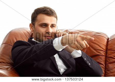 Portrait of handsome businessman in suit talking phone shows a finger forward sitting on the sofa isolated on white