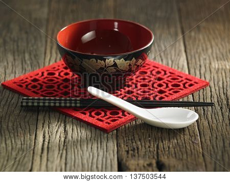 Chopsticks and bowl for rice on wooden background